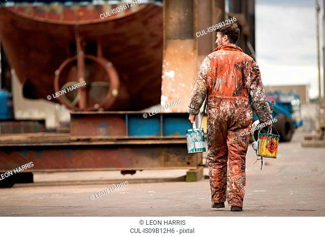 Rear view of male ship painter carrying paint cans in ship painters yard