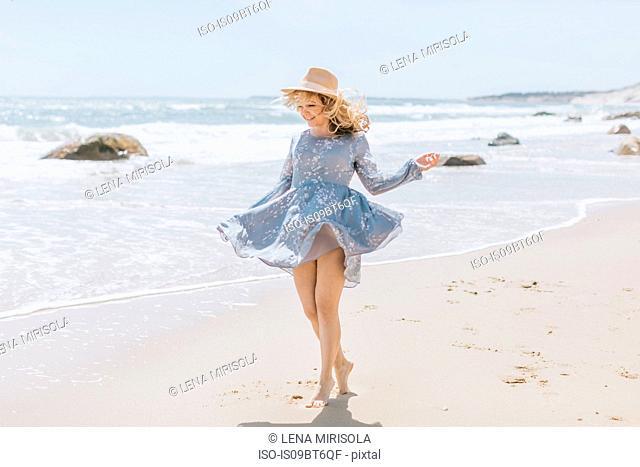 Young woman dancing on windy beach, Menemsha, Martha's Vineyard, Massachusetts, USA