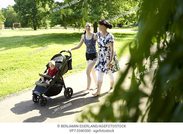 mother and grandmother walking with baby toddler child in buggy outdoors in park