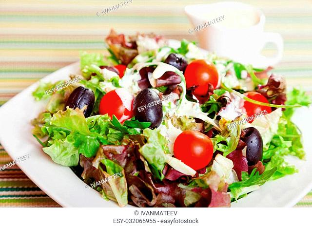 Fresh salad with cherry tomatos, black olives and mayonnaise dressing