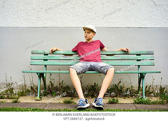 teenage boy sitting on the bench. German ethnicity. In south Bavaria, Germany