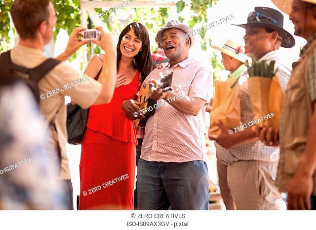 Tourist taking photograph of friend posing with market trader playing ukulele