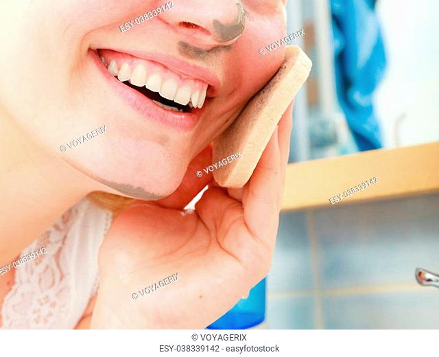 Beauty procedures spa and skin care concept. Young woman removing facial clay mud mask with sponge in bathroom