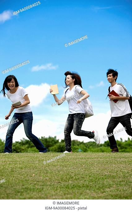 Young adults running on the lawn and laughing