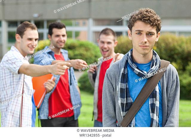Lonely student being bullied by group of brutish classmates looking hopelessly at the camera