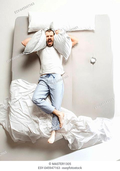Top view photo of young man sleeping in a big white bed. Emotions concept. Morning after sleep. Happy man on the bed. alarm clock and unwillingness to wake up