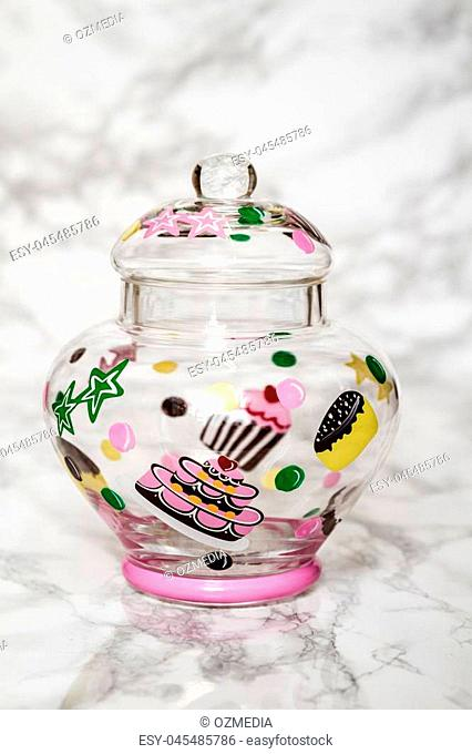 Colorful empty glass jar on white marble background