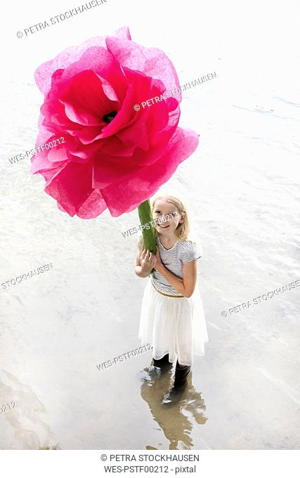 Portrait of smiling blond girl standing in a lake holding oversized pink artificial flower
