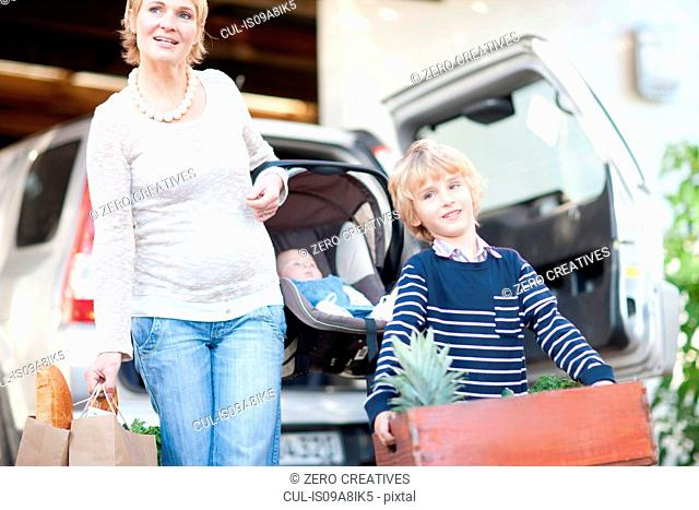 Mother with baby car seat and son carrying box of plants