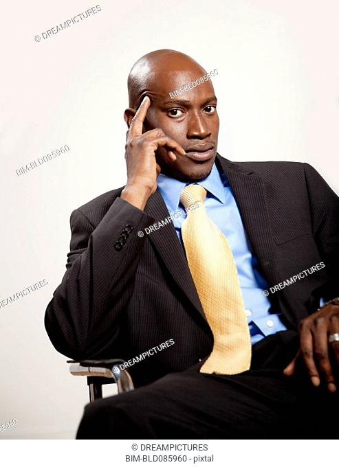Serious African American businessman sitting in chair