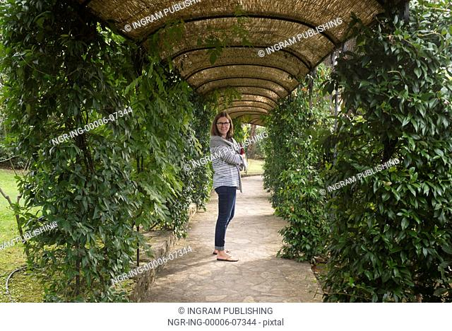 Happy woman standing on covered garden path, Gaiole in Chianti, Tuscany, Italy