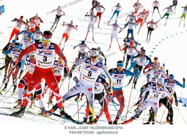 Alex Harvey from Canada (l) leads the field during the men's 50 km mass start freestyle cross-country event at the Nordic Ski World Championship in Lahti