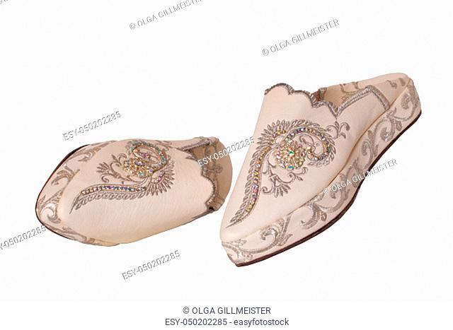 Slippers woman isolated. Closeup of elegant luxurious handmade beige ladies slippers with beautiful floral embroidery and rhinestones