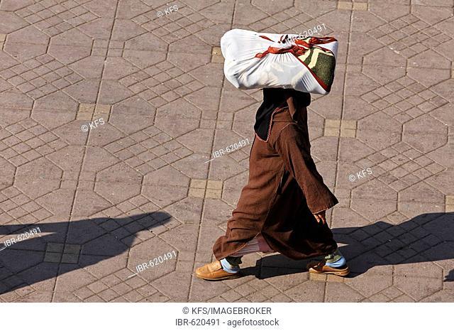 Woman wearing a djellaba carrying a parcel on her head, Djemaa el Fna, Marrakech, Morocco, Africa
