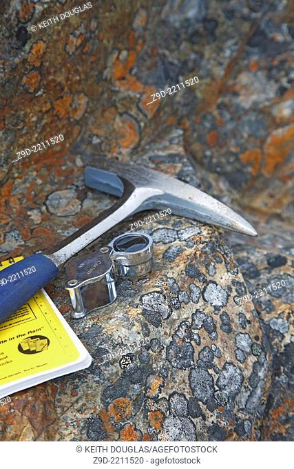 Mining exploration concept image of rock hammer, notebook, and magnifier