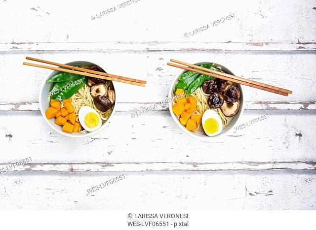 Ramen with noodles, egg, hokkaido pumpkin, mung sprout, shitake mushroom in bowl, chopsticks