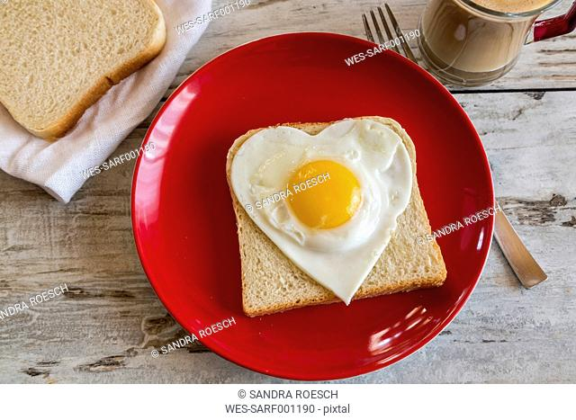 Heart-shaped fried egg on toast on red plate