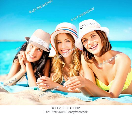 summer holidays, vacation, travel and people concept - group of smiling young women in hats lying over exotic tropical beach background