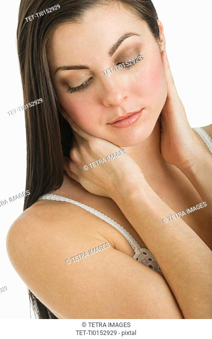 Studio shot of young woman caring for skin