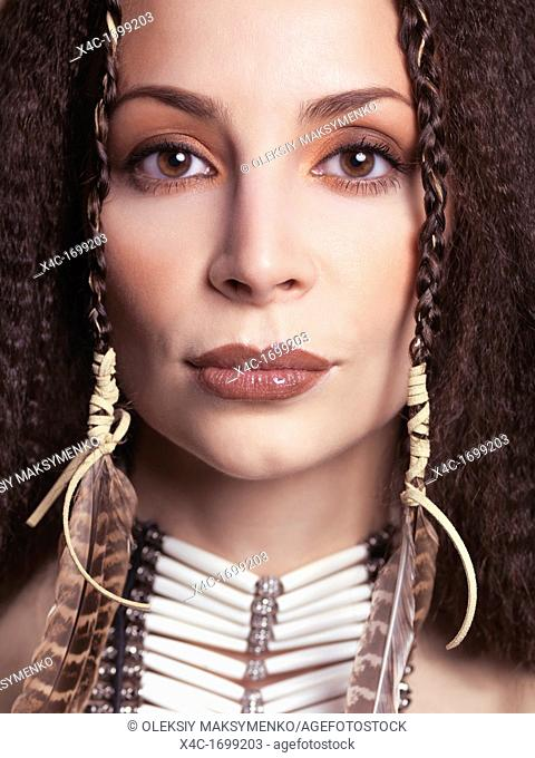 Artistic closeup beauty portrait of a woman wearing aboriginal native accessories necklace and feathers in her hair