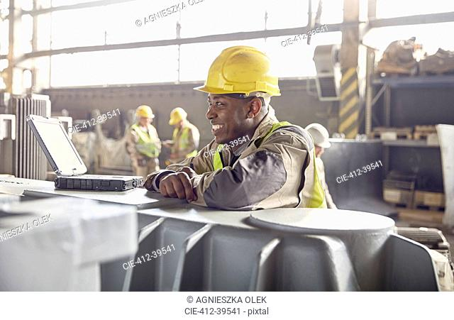 Smiling steelworker looking away in steel mill