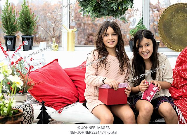 Two girls opening Christmas presents