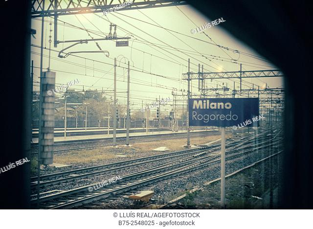 View from the window of a train of the arrival at the station Rogodero, Milano, with rail tracks, electrical wires, poles and a sign post