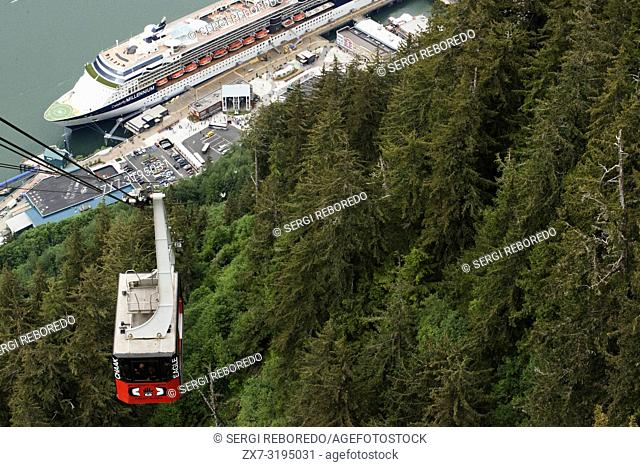 Mount Roberts Tramway in Juneau dock, Alaska, USA. Juneau downtown, city. Alaska. USA. Celebrity Millennium cruise ship docked between snow capped mountains and...