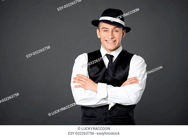 Young male confident male posing in gangster style suite. Studio isolated on gray background