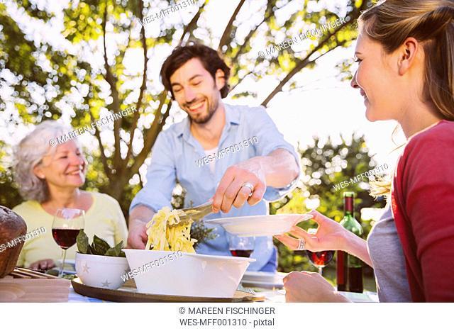 Couple and senior woman having dinner in garden