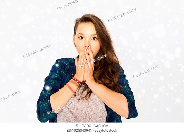 winter, christmas, people, emotion and teens concept - scared teenage girl over gray background and snow