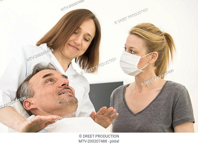 Female dentist consoling patient with dental assistant, Munich, Bavaria, Germany
