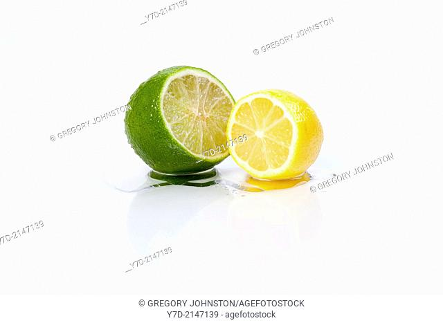 A close up of a lemon and lime sliced open on a white background