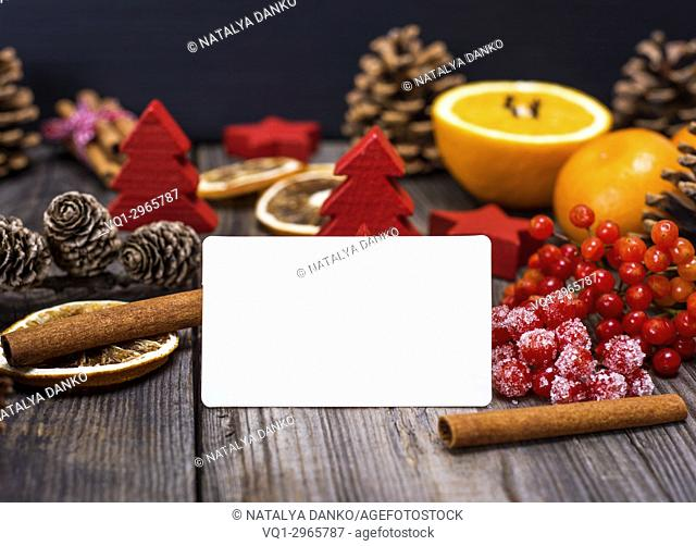empty white business card on a gray wooden background in the middle of a Christmas decor