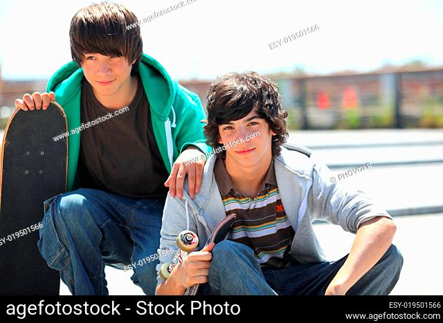 Portrait of two boys smiling with a skateboard
