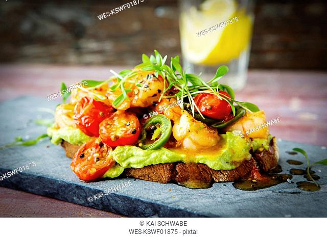 Crostini with shrimps and tomatoes, roasted bread, herbs, avocado cream, sweet chili sauce, jalapenos, cress