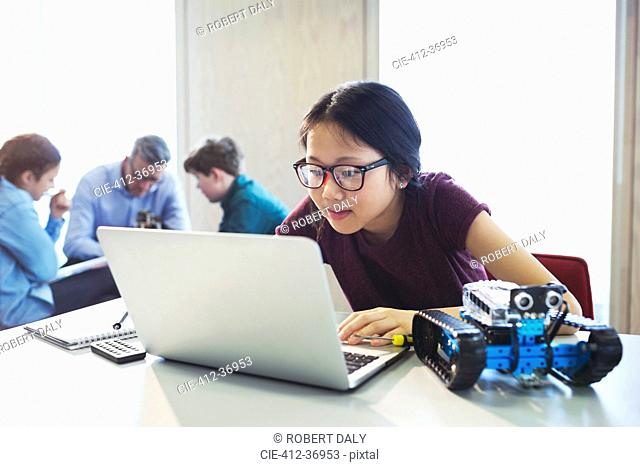 Focused girl student programming robotics at laptop in classroom