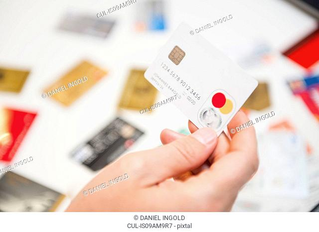 Mid adult man holding credit card, close-up