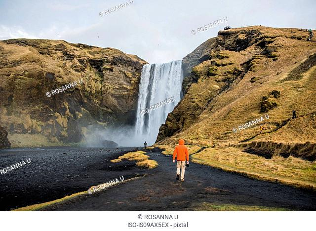 Rear view of people walking on volcanic landscape to waterfall, Skogafoss, Iceland