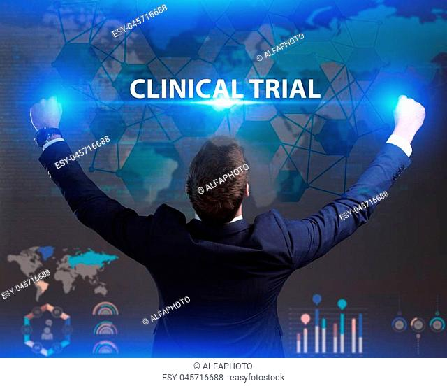 The concept of business, technology, the Internet and the network. Young businessman showing inscription: Clinical trial