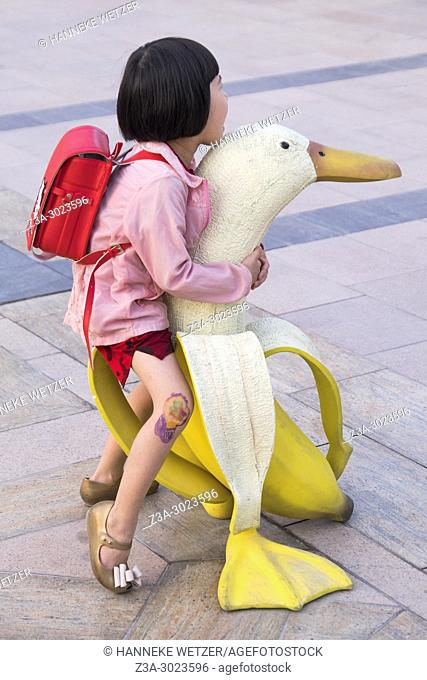 Little girl posing on a banana duck street art in Dubai