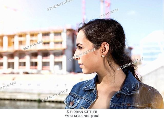 Germany, Berlin, profile of young woman in front of construction site