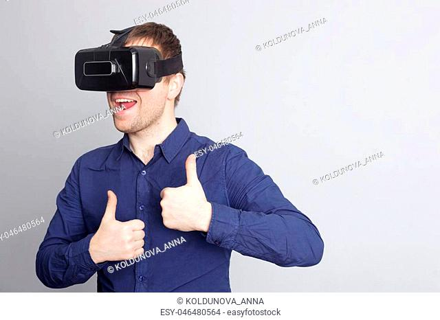 Young man with glasses of virtual reality in casual clothes looks forward and shows thumbs up