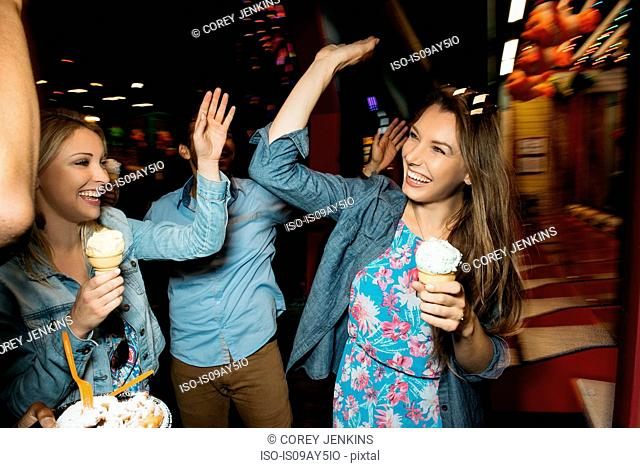 Adult friends high fiving each other in amusement park at night, Santa Monica, California, USA