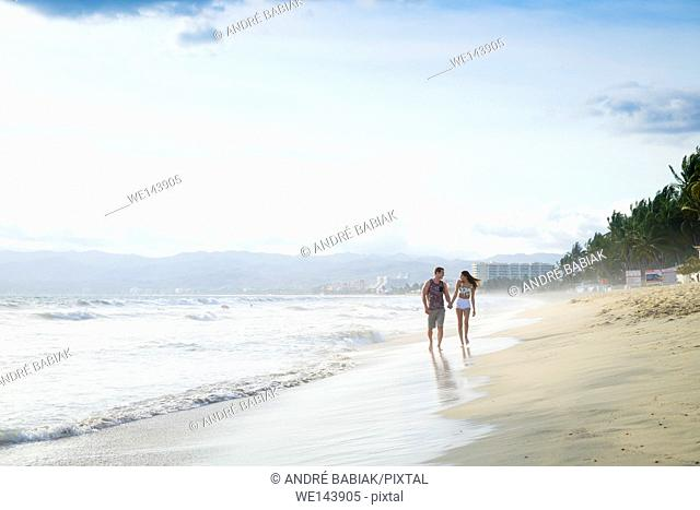 Young couple walking on lonely beach - Riviera Nayarit, Mexico