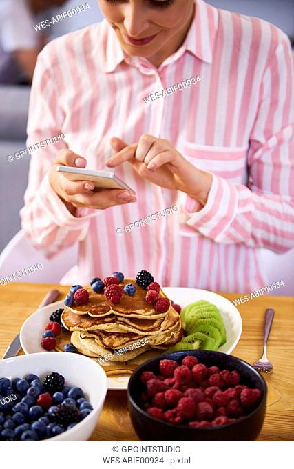 Young woman using smartphone at breakfast