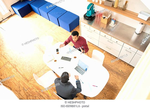 Overhead view of two businessmen meeting at office table