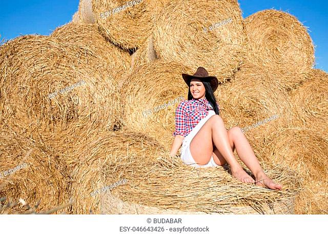 Beautiful young woman with hat and black long hair in white shorts and plaid shirt sitting on bale of straw in the field and enjoying on sun