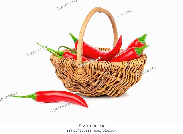 Red chili pepper in a wicker basket, isolated on white background