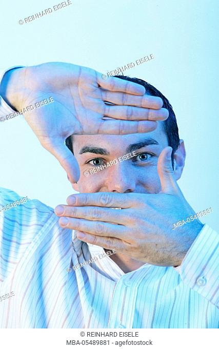 Man forms a rectangle with his hands and looks through